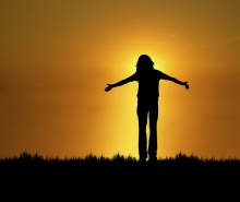 silhouette of woman with open arms at sunset