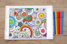 Coloring page with coloring in pens on a wooden background.Creative lifestyle concept
